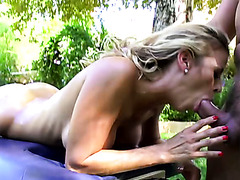 Busty oiled up MILF gives steamy blowjob to her massage man outdoors
