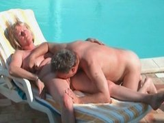 Two grannies pleasing each other near the pool
