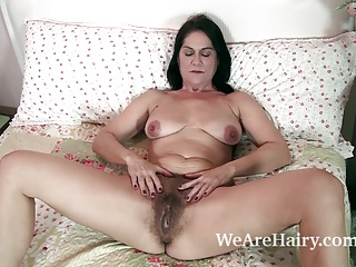 The sexy and mature MILF Kaysy strips in bed